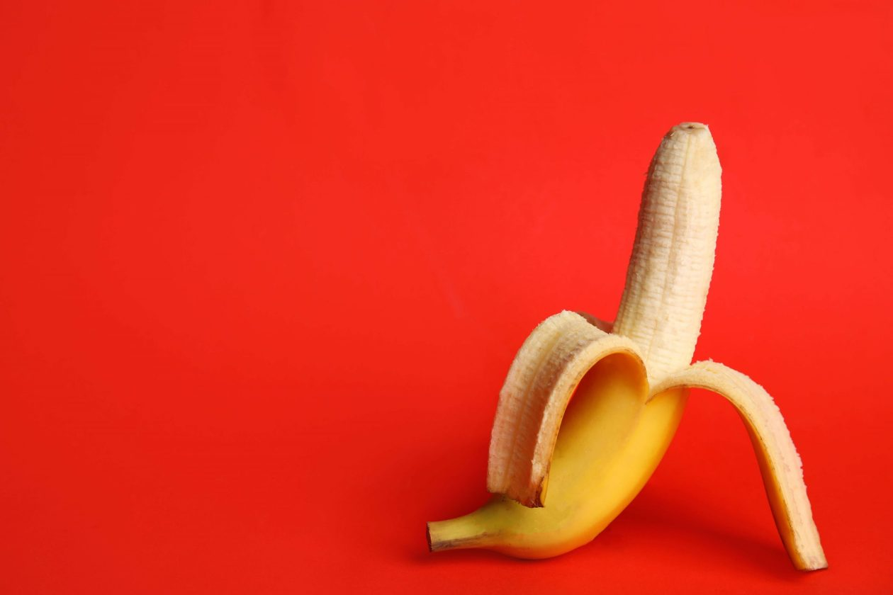 Banana on a red background, encouraging you to think of an erect dick. Photo.