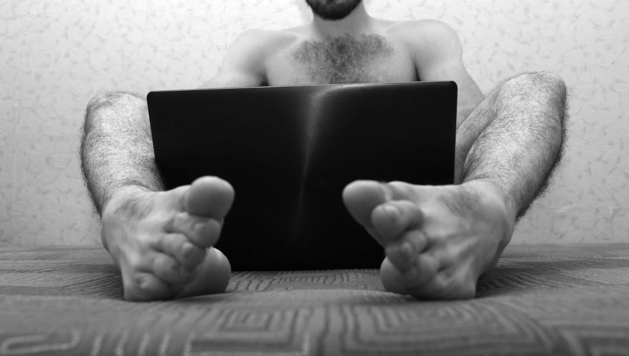 Naked man with hairy legs sits on floor with laptop between legs covering his junk. Photo.