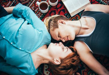 A queer couple lying on the floor next to each other, looking at each other and smiling. Photo.