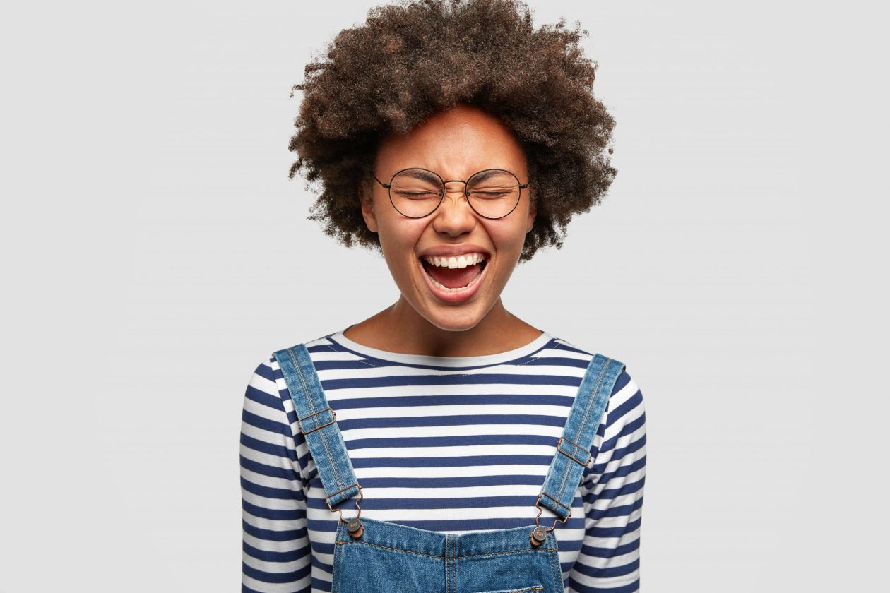 A black afab person in dungarees, a stripy top and glasses grins at the camera with their eyes closed. Photo.