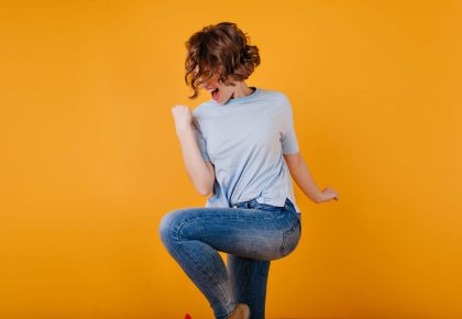 Short-haired afab person wearing dark-blue jeans dances in celebration. Photo.