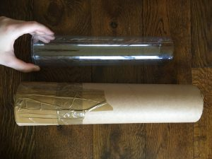 A Clone-A-Willy clear plastic tube alongside a bigger cardboard tube. Photo.
