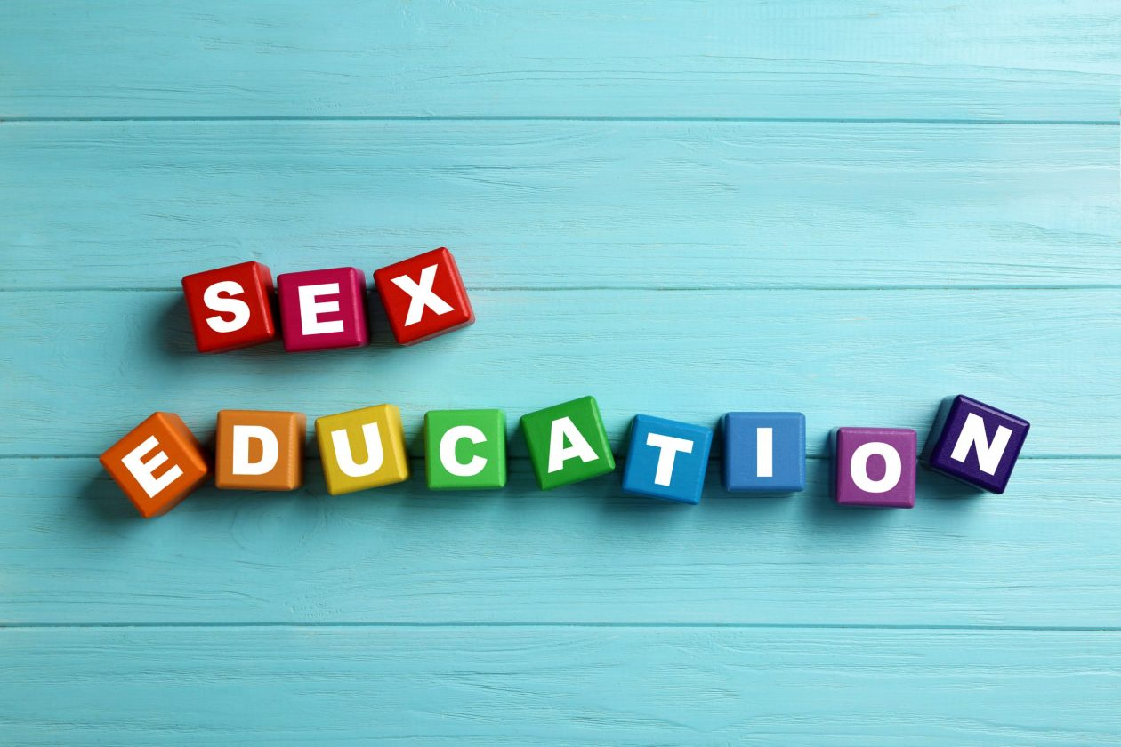 """Colourful wooden blocks with phrase """"SEX EDUCATION"""" on light blue background. Photo."""