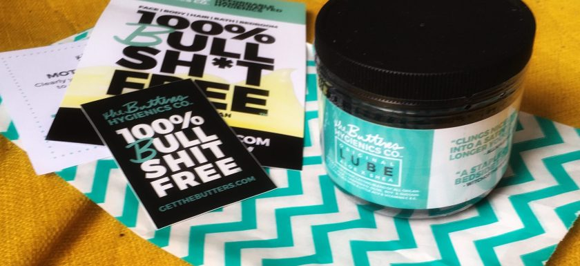 A pot of lube with a turquoise wrapper around it, plus a load of stickers, sits on a yellow sofa. Photo.