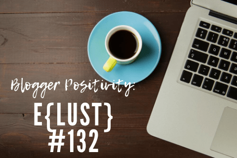 A laptop and blue coffee cup sit on a wooden desk, next to white writing reading 'blogger positivity: eLust'. Photo.