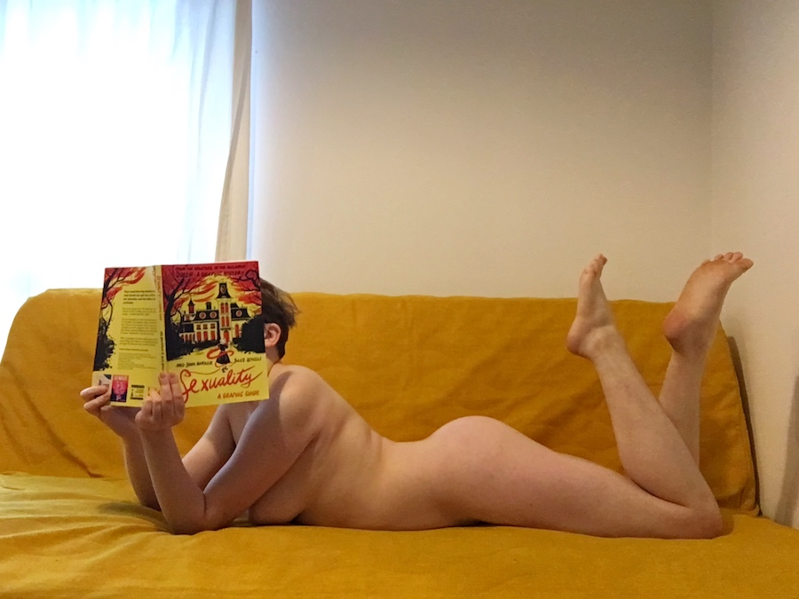 A trans guy lies naked on a yellow, his feet kicked up cutely and a book held up to cover his face. Photo.
