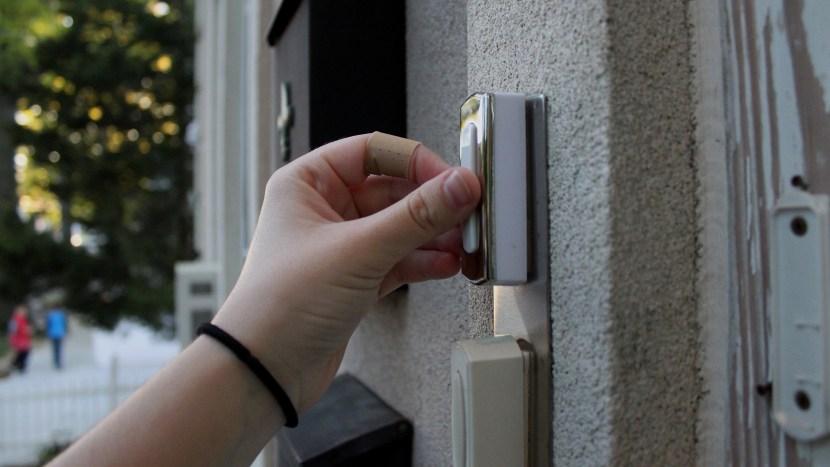 Een hand die een deurbel indrukt voor collecte