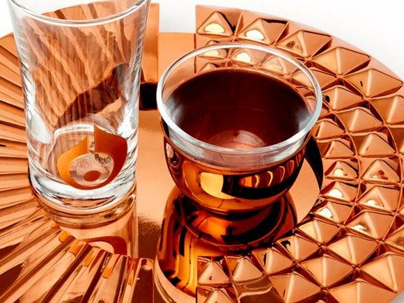 Gold tray holding fancy coffee and tea tumblers.