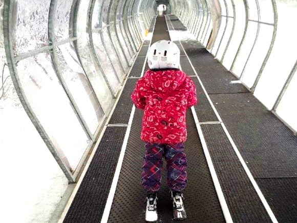 Young girl dressed in ski gear riding the carpet lift.
