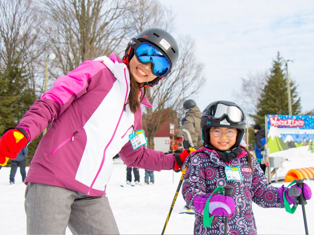 A young woman and a young girl learning to ski.