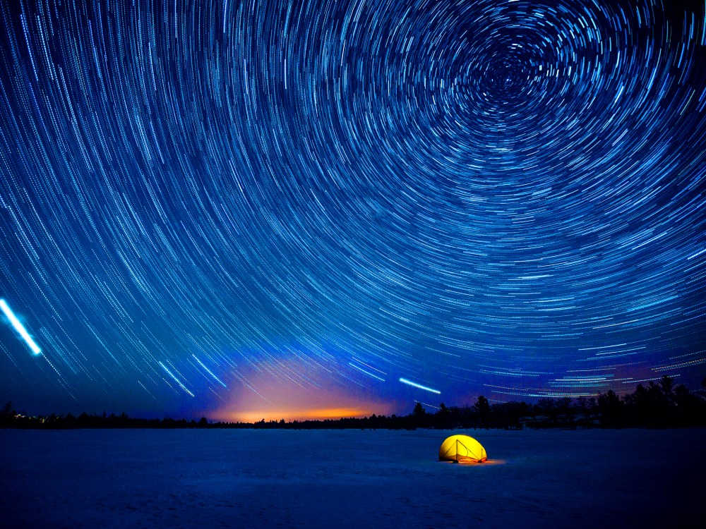 Stunning starry sky shining over a lone tent in winter.