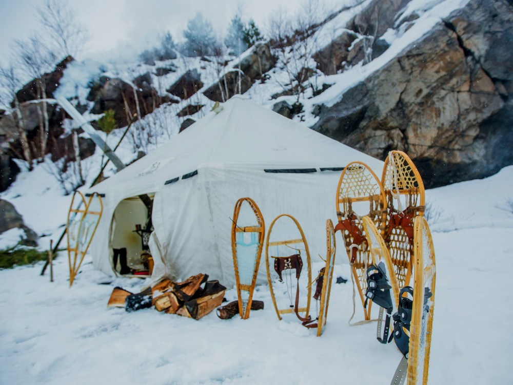 Winter camping tent with snowshoes set up outside