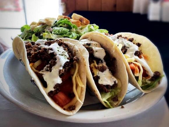 Close up of three tacos and salad
