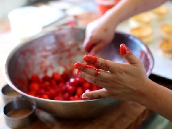 A person baking with fresh berries