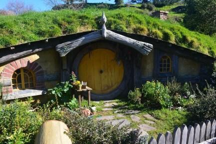 Een hobbithuisje. Een huisje in een heuvel met een gele ronde deur.