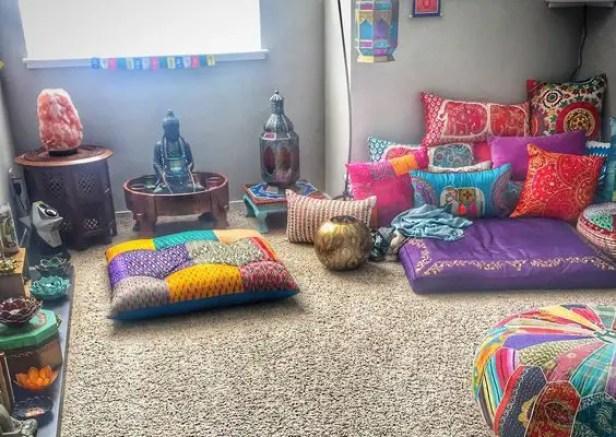 Ingerichte meditatiekamer met kussen en een Boeddhabeeld.