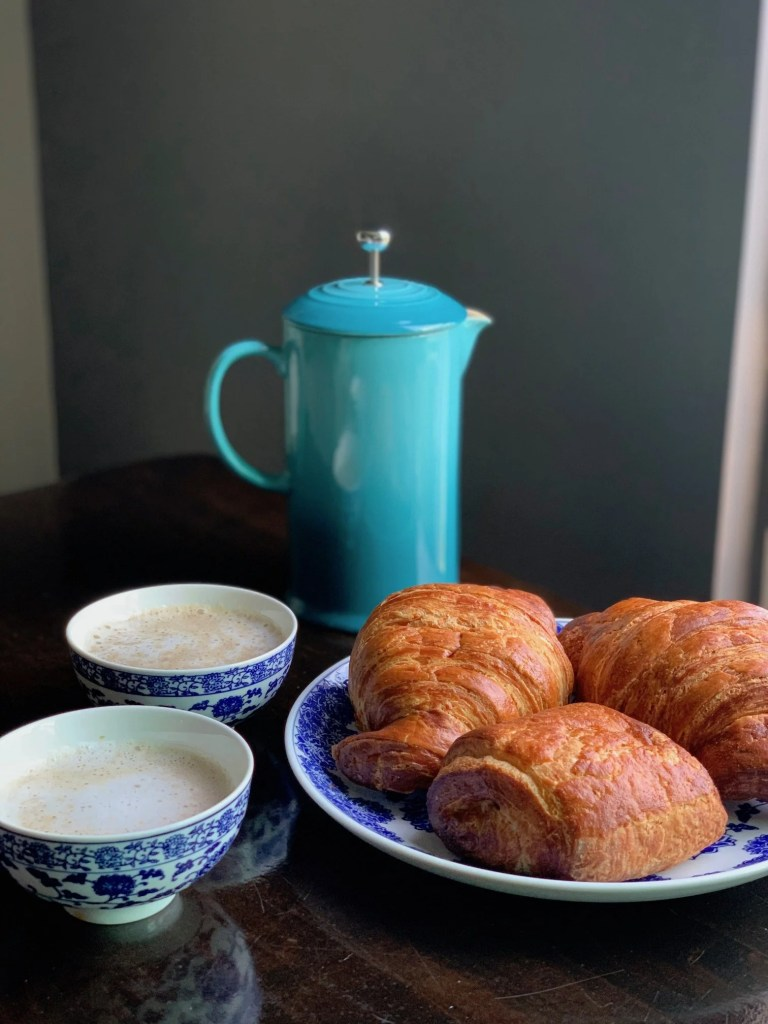 cafe au lait and a blue French press and croissants with pain au chocolat