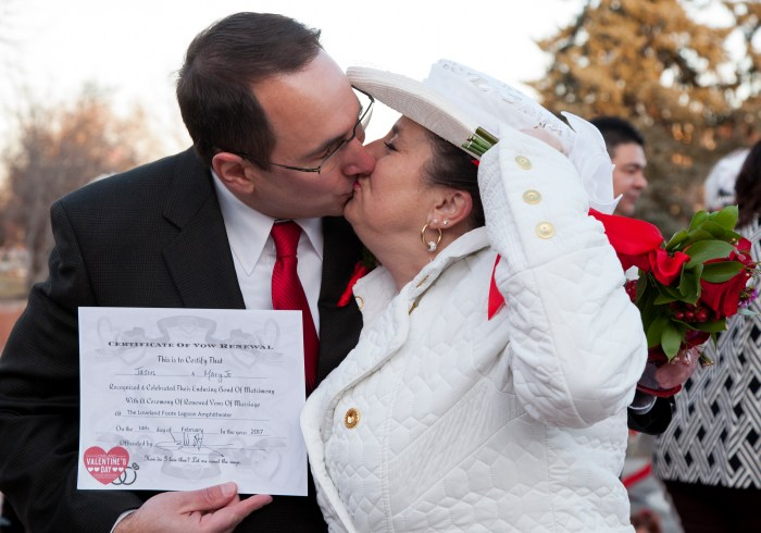 Join On The Rocks mobile bar and tap at the 4th Annual Valentine's Day Group Wedding in Loveland CO! Photo shows a couple who were married at the event kissing and holding their marriage certificate.