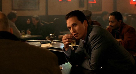 John Turturro in Thirteen Conversations About One Thing. Walker, a white Italian American man with slicked back dark hair and a sharp grey suit, is at a dimly lit but crowded pub, leaning over the bar, staring intently at someone out of the frame.