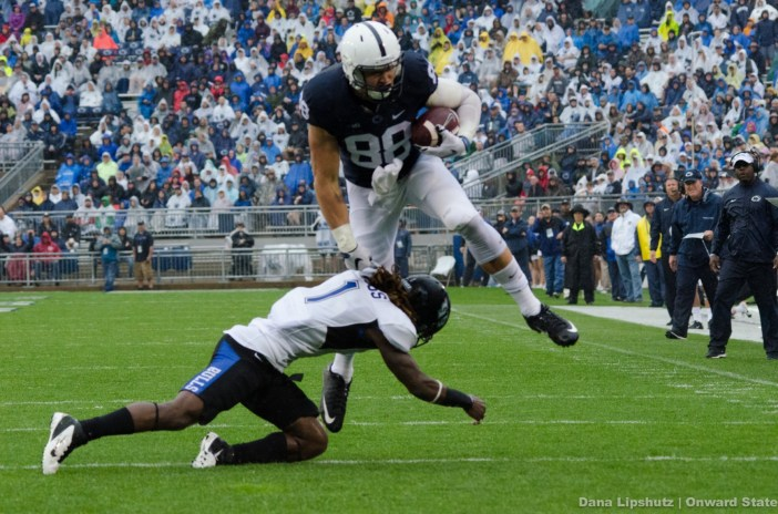 Mike Gesicki leaps over Bull's cornerback after a completed pass.