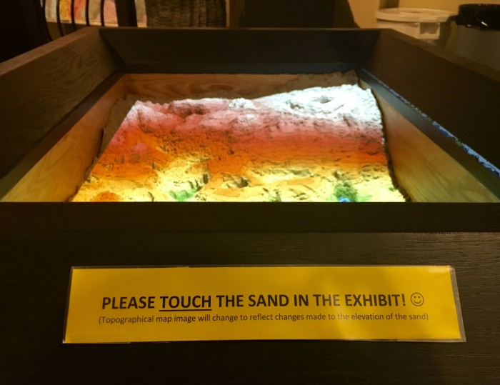 Contrary to the rules of most museums, visitors are encouraged to touch the sand in the Augmented Reality Sandbox to learn more about how topographical maps work.