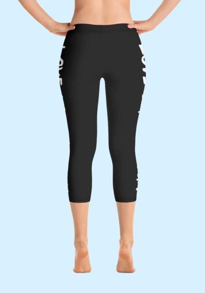 """Woman wearing Capri Zouk Leggings decorated with a unique """"Love Dance Zouk"""" design. Back view (1) barefoot. By Ooh La La Zouk."""