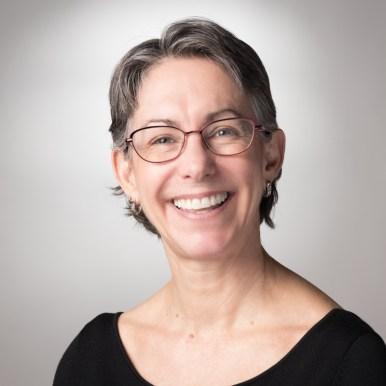 woman headshot gray background smiling