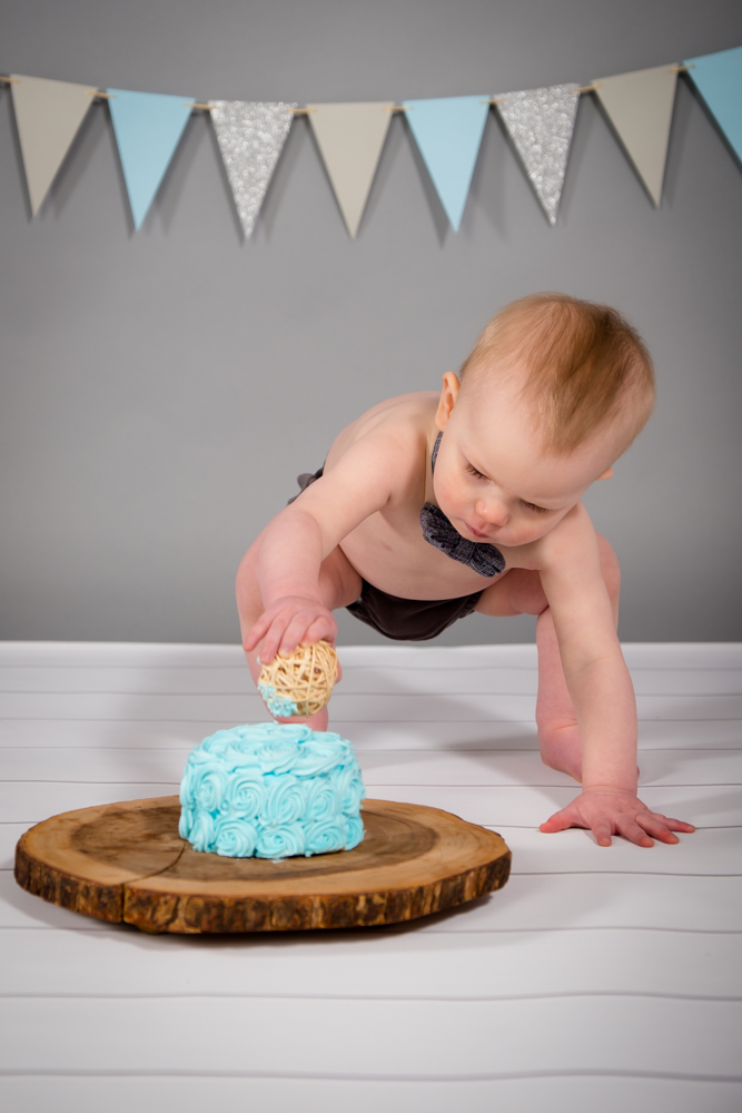 Boy playing with his blue smash cake