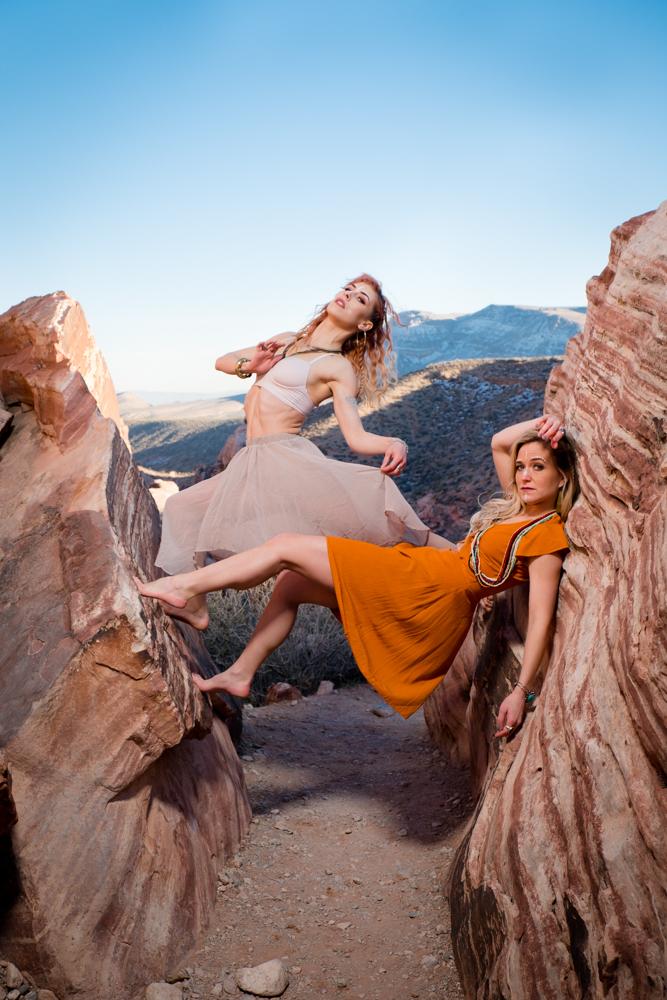 Two dancers dangling between two large rocks