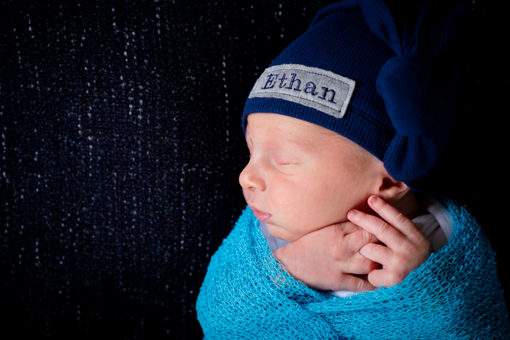 "Newborn boy wrapped in a blue wrap with a hat that says ""Ethan"""