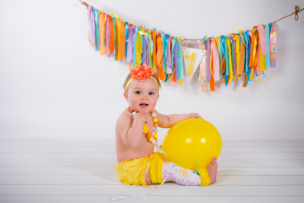 Baby girl sitting with her yellow balloon
