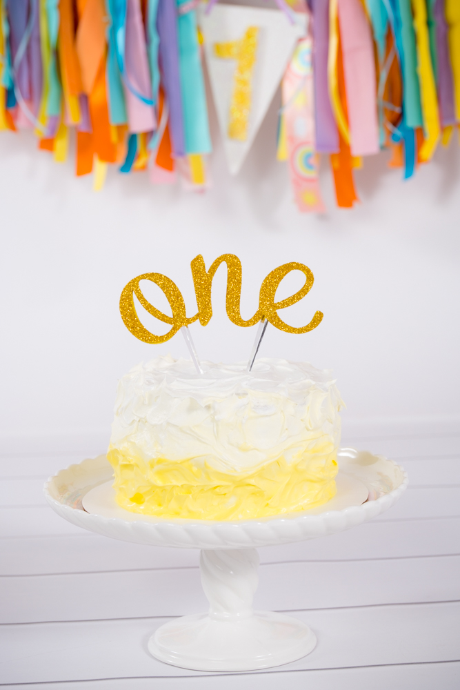 "Yellow ombre cake with ""one"" written on it"