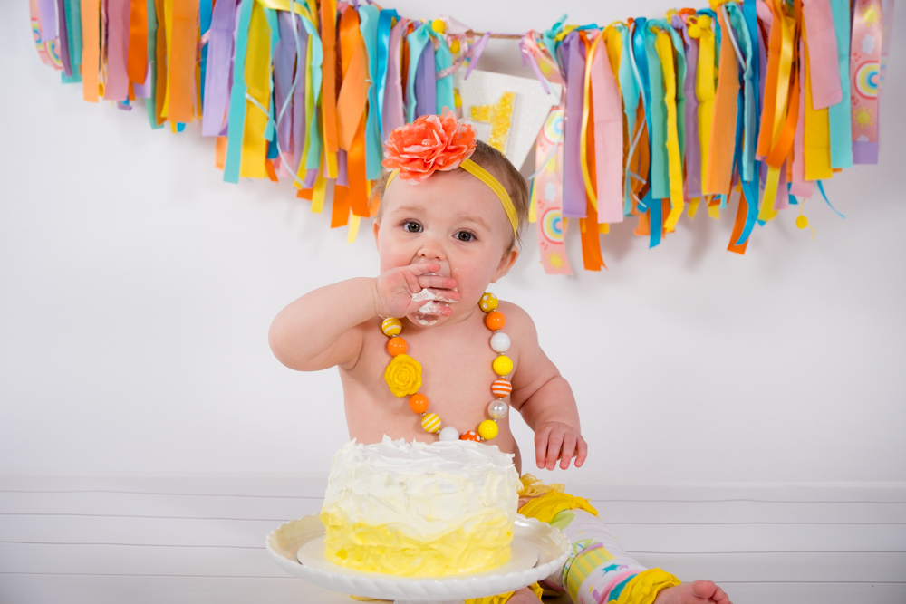 Birthday girl with a small handful of cake