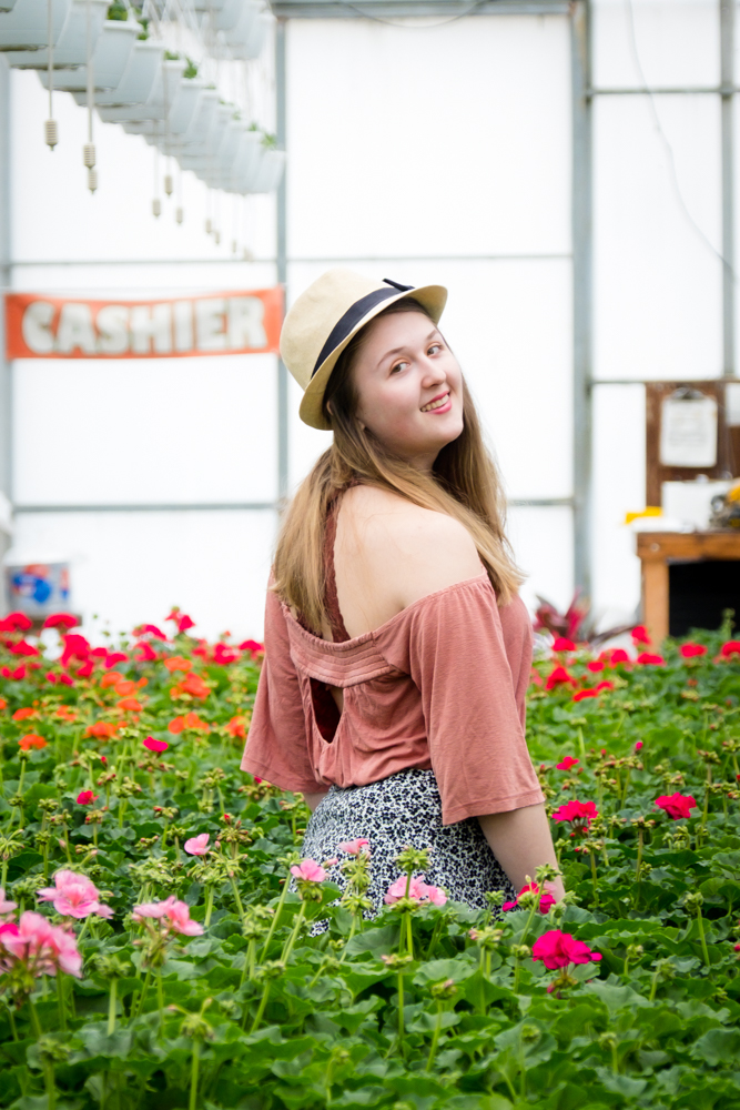 High School senior in a hat surrounded by flowers