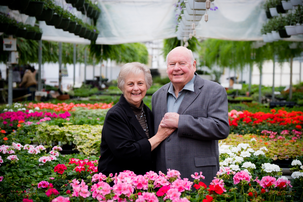 Older couple loving posing among flowers