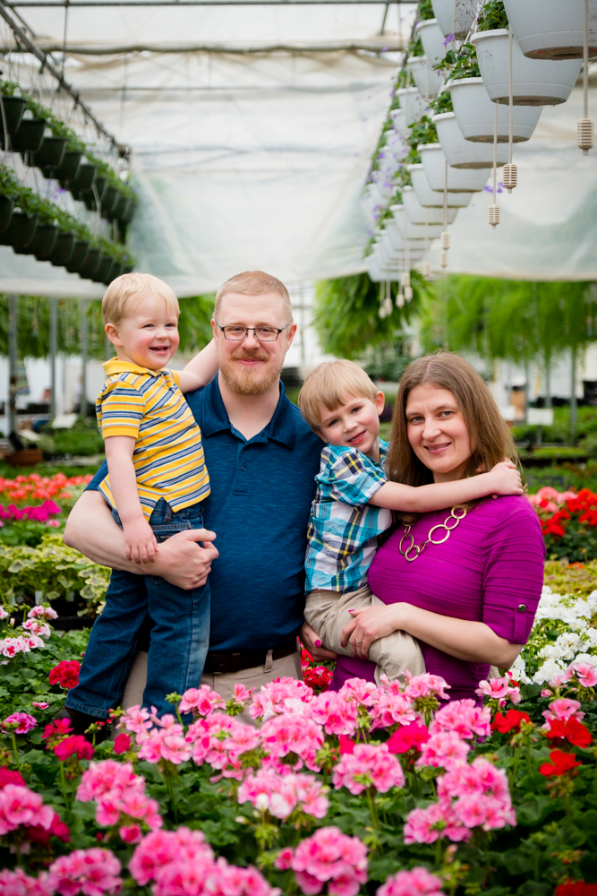Family of 4 smiling in the greenhouse flowers