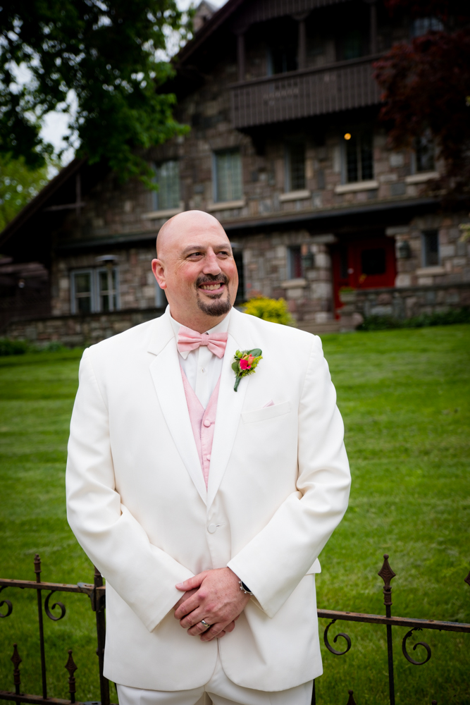 Groom in a white tux with orange boutonniere