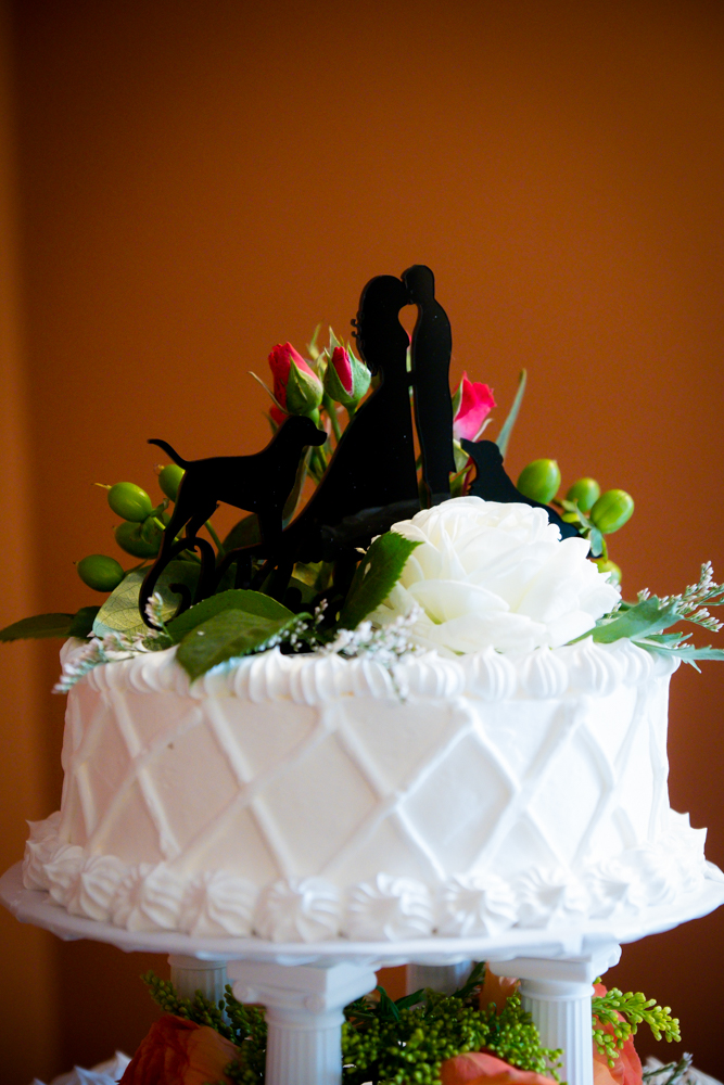 Wedding cake topper of bride and groom with two dogs
