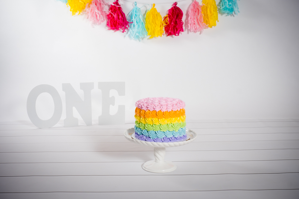 Rainbow cake with colorful decorations and the letters O-N-E