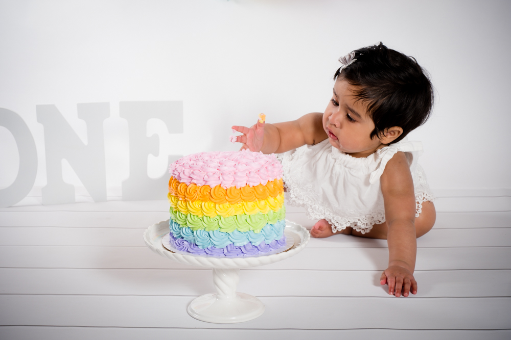 Little girl touching her rainbow cake.
