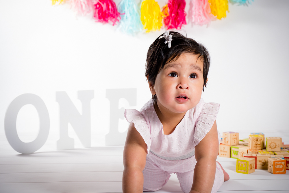 One year old girl crawling forward with colorful decorations behind her.