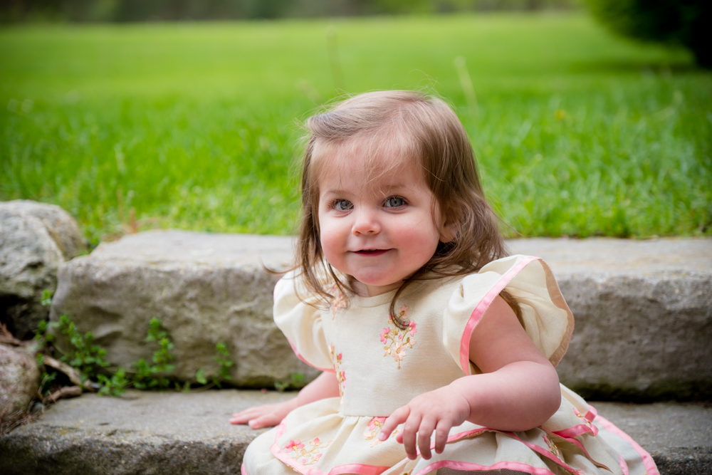 baby girl smiling on rock steps