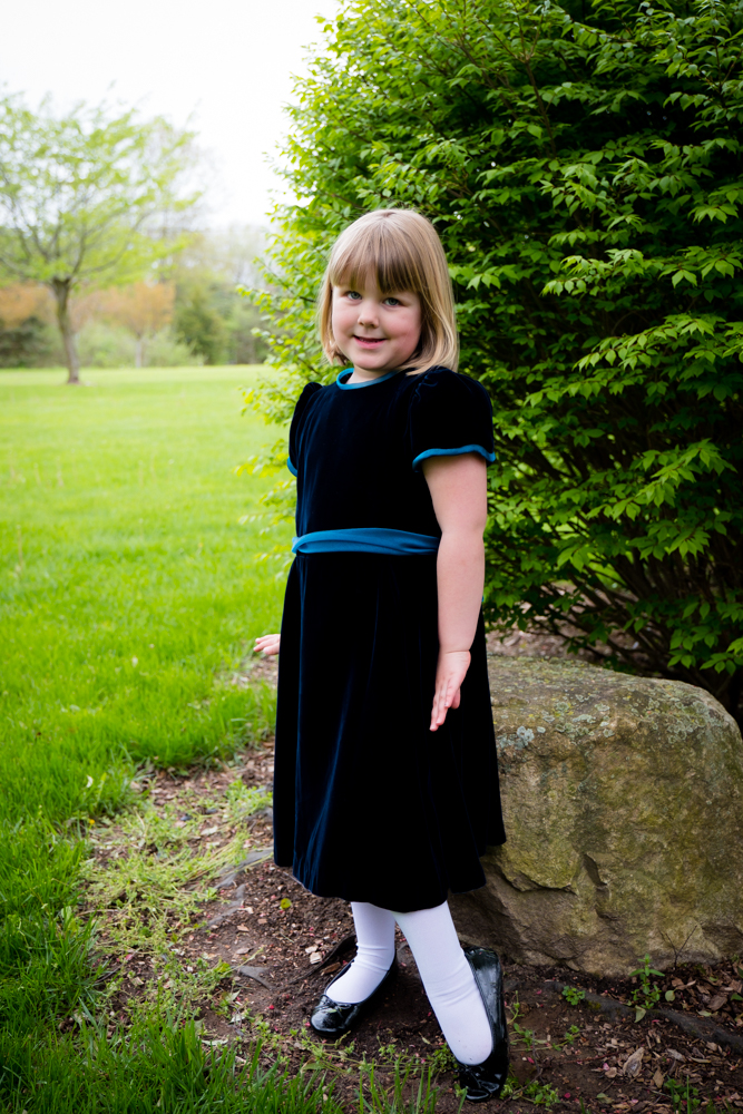 Young girls standing pretty in a blue velvet dress