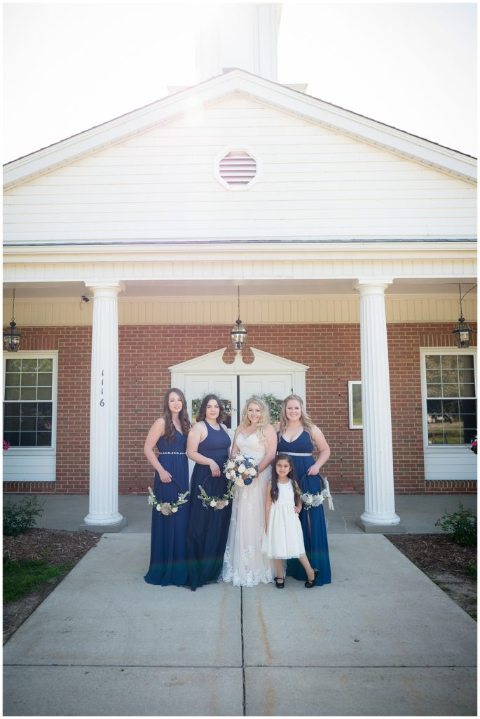 Bride with her bridesmaid and flower girl in front of the church.