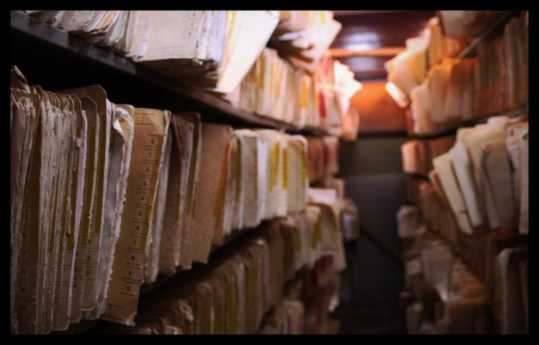 file folders filled with paper on shelves