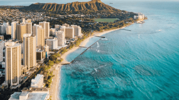 Aerial shot of a beach in Hawaii beside a city and a mountain.