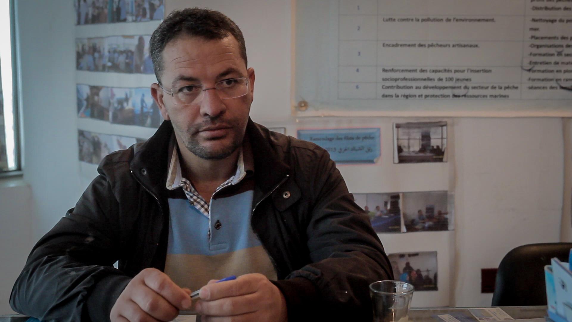 Chamseddine Bourassine, presidente dell'associazione pescatori, nella loro sede dove sono appese le fotografie dei salvataggi di migranti (foto: Giulia Bertoluzzi)