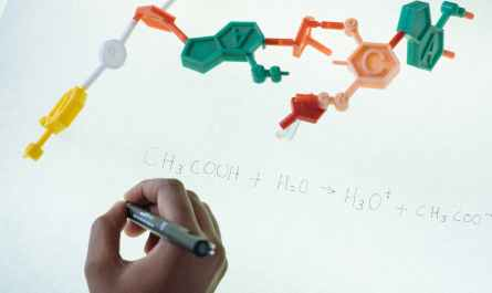 crop ethnic clever student writing formula after analysis of molecule model in university