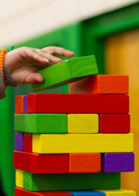 Image of child's hand placing green block on a well defined building that is constructed by other color blocks.