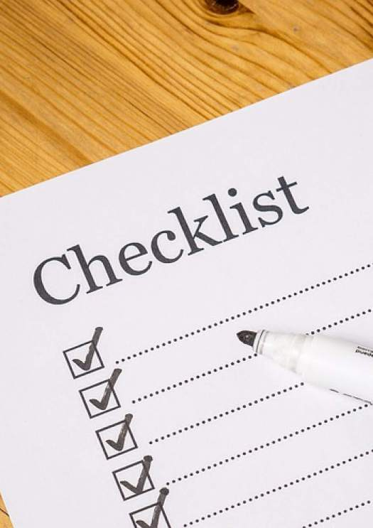 Image of a sheet which say checklist with a marker placed on a wooden board